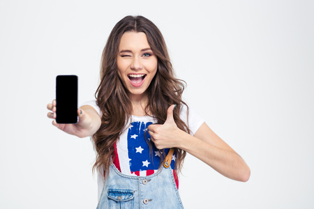 Photo pour Portrait of a cheerful woman showing blank smartphone screen and showing thumb up isolated on a white background - image libre de droit