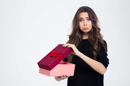 Foto de Portrait of a sad woman standing with opened gift box isolated on a white background and looking at camera - Imagen libre de derechos