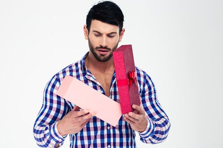 Photo pour Portrait of a young man opening gift box isolated on a white background - image libre de droit