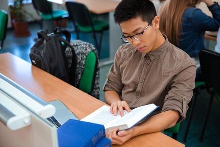 Photo pour Portrait of a male student reading book in classroom - image libre de droit