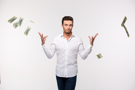 Photo for Portrait of a young man throwing money in the air isolated on a white background - Royalty Free Image