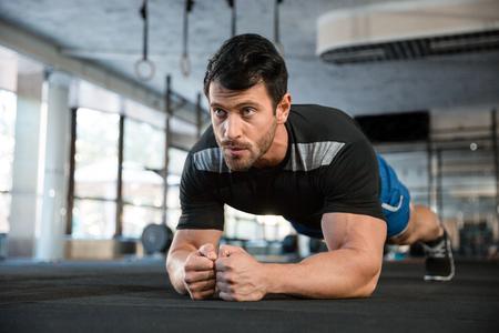 Foto de Athlet wearing blue shorts and black t-shirt making static exercise - Imagen libre de derechos
