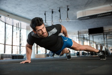 Foto de Portrait of a handsome man doing push ups exercise with one hand in fitness gym - Imagen libre de derechos