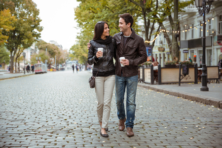Photo for Portrait of a happy romantic couple with coffee walking outdoors in old european city - Royalty Free Image
