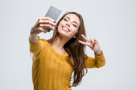 Foto per Portrait of a smiling cute woman making selfie photo on smartphone isolated on a white background - Immagine Royalty Free