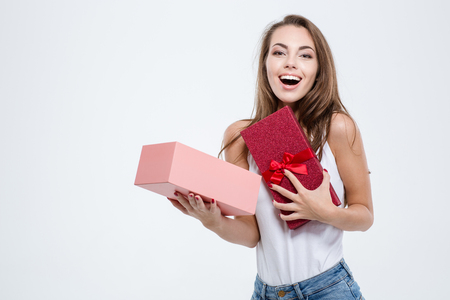 Foto de Portrait of a cheerful woman opening gift box isolated on a white background - Imagen libre de derechos