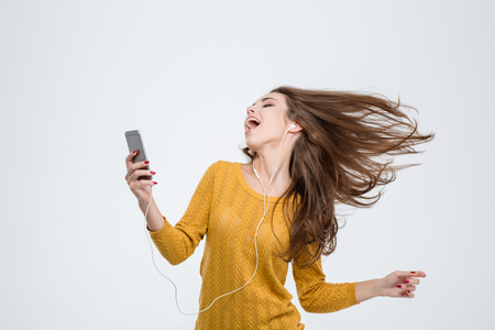 Photo for Portrait of a cheerful cute woman listening music in headphones and dancing isolated on a white background - Royalty Free Image