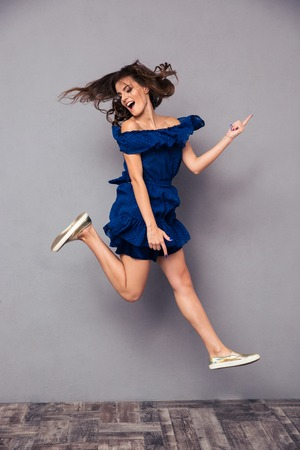 Foto de Portrait of a funny cheerful woman jumping on gray background - Imagen libre de derechos