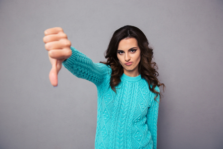 Foto de Portrait of a young woman showing thumb down over gray background - Imagen libre de derechos