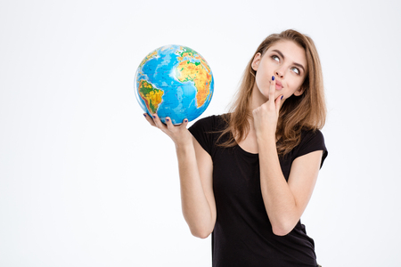 Photo for Portrait of a thoughtful woman holding world globe and looking up isolated on a white background - Royalty Free Image