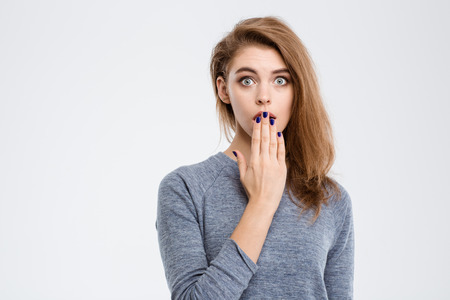 Photo pour Portrait of amazed woman covering her mouth with palm isolated on a white background - image libre de droit