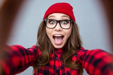 Foto de Portrait of a cheerful woman making selfie photo over gray background - Imagen libre de derechos
