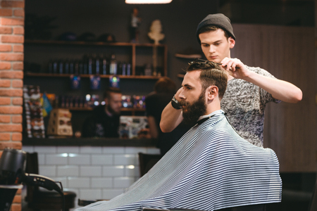 Foto de Young handsome barber making haircut of attractive bearded man in barbershop - Imagen libre de derechos