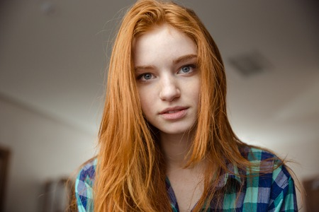 Photo pour Portrait of thoughtful attractive redhead young woman in plaid shirt looking camera - image libre de droit