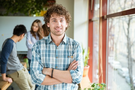 Photo pour Attractive positive curly young male in checkered shirt posing in office with folded hands standing near the window - image libre de droit