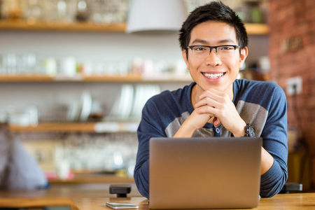 Photo for Portrait of positive asian male in glasses with laptop in cafe - Royalty Free Image