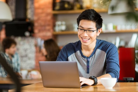 Foto de Happy cheerful young asian male in glasses smiling and using laptop in cafe - Imagen libre de derechos