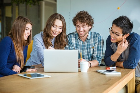 Foto de Group of positive cheerful students using laptop and doing homework together in classroom - Imagen libre de derechos