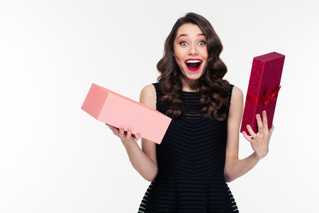 Happy amazed retro styled woman with curly hair in black dress opened present over white background