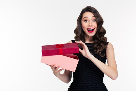 Excited cheerful attractive young woman with retro hairstyle in black dress opening gift over white background