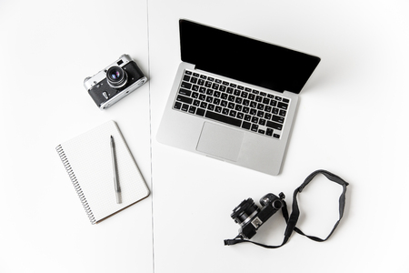 Foto de Top view of two cameras, notepad with pen and blank screen laptop isolated over white background - Imagen libre de derechos