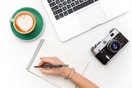 Photo pour Top view of laptop, old camera, cup of coffee and woman hand writing in notebook over white background - image libre de droit