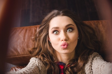 Foto de Portrait of a young woman lying on the sofa and making selfie photo while kissing at camera - Imagen libre de derechos