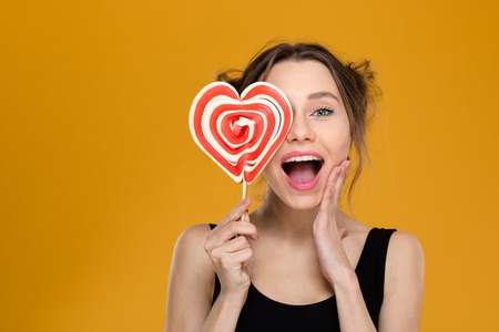 Photo for Happy excited young woman covered her eye with bright heart shaped lollipop over yellow background - Royalty Free Image