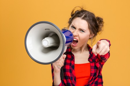 Foto de Annoyed furious young woman in checkered shirt shouting in loudspeaker and pointing on you over yellow background - Imagen libre de derechos