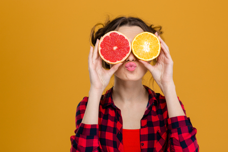 Photo for Funny playful young woman in checkered shirt holding halves of citrus fruits against her eyes and making duck face over yellow background - Royalty Free Image