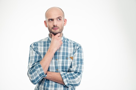 Foto de Attractive thoughtful young man in plaid shirt looking away over white background - Imagen libre de derechos