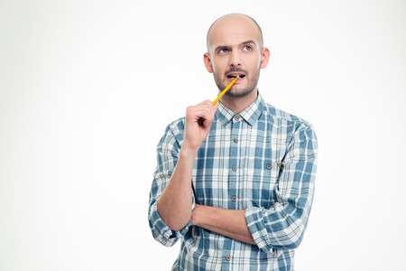Pensive handsome young male in plaid shirt with pencil in his mouth isolated over white background