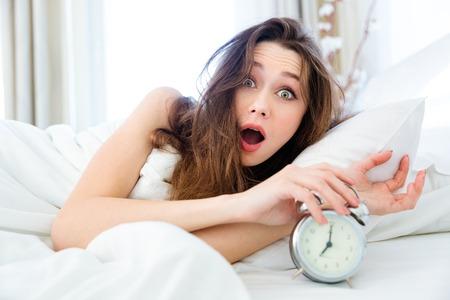 Photo pour Shocked young woman waking up with alarm - image libre de droit