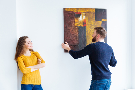 Photo pour Young couple hanging picture on the wall at home - image libre de droit