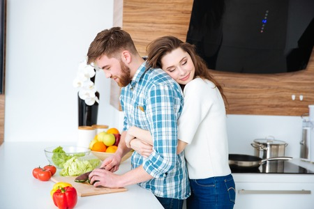 Photo pour Tender woman hugging her husband while he cutting vegetables for salad on the kitchen - image libre de droit
