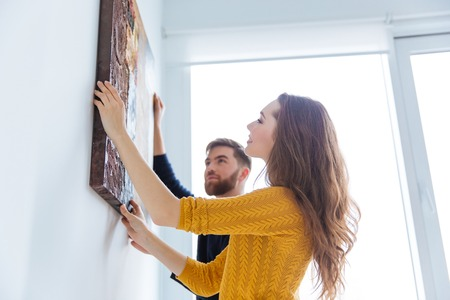 Photo pour Happy couple hanging picture on the wall at home - image libre de droit