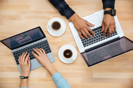 Photo pour Top view of hands of african man and caucasian woman typing on two laptops and drinking coffee on wooden table - image libre de droit