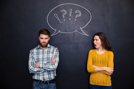 Foto de Frowning offended young couple standing with arms crossed after argument over chalkboard background - Imagen libre de derechos