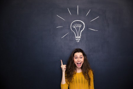 Photo pour Cheerful young woman with opened mouth pointing up  and having an idea over blackboard background - image libre de droit