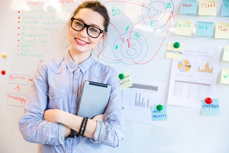 Photo pour Happy businesswoman in glasses looking at camera with whiteboard on background - image libre de droit
