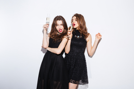 Photo pour Two attractive women in night dress drinking champagne isolated on aw hite background - image libre de droit