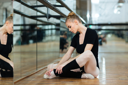 Photo for Injured ballerina in pointes sitting on the floor in ballet class - Royalty Free Image