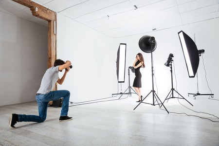 Foto de Photographer working with model in studio with equipments - Imagen libre de derechos