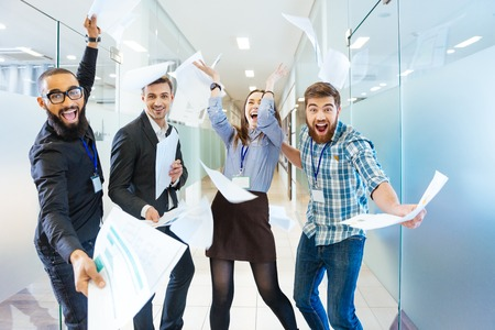 Foto de Group of joyful excited business people throwing papers and having fun in office - Imagen libre de derechos
