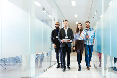 Foto de Full length of group of happy young business people walking the corridor in office together - Imagen libre de derechos