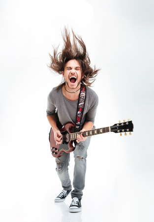 Photo for Crazy young man shaking head and playing electric guitar over white background - Royalty Free Image