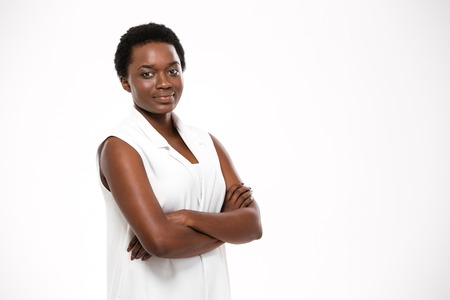 Foto de Smiling confident african american young woman standing with arms crossed over white background - Imagen libre de derechos