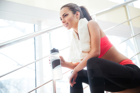 Photo for Happy beautiful young sportswoman resting and drinking water on stairs in gym - Royalty Free Image