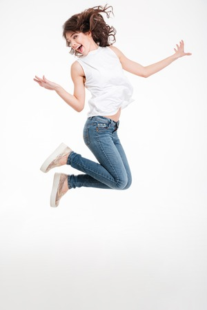 Foto de Full length portrait of a cheerful woman jumping isolated on a white background - Imagen libre de derechos