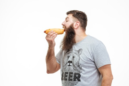 Photo for Profile of handsome man with beard standing and eating hot dog over white background - Royalty Free Image